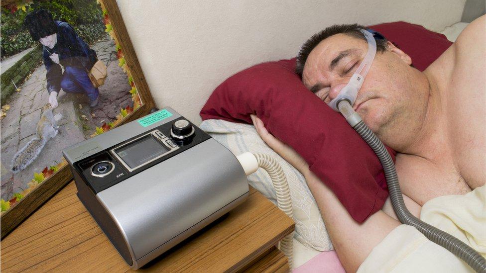Hombre usando máquina para respirar.